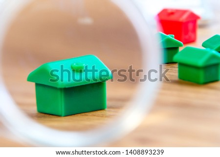 closeup of small house using a magnifier, loupe as a buying new dreamy perfect house for me #1408893239