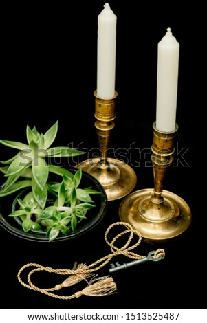 closeup of small old key with long golden cord and tassels lying in front of green plant and two brazen antique candlesticks with white candles isolated on black background