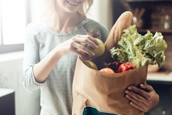 Closeup of Smiling Girl holds Bag of Healthy Food. Close up of Beautiful Woman Laying out Fresh Organic Fruits and Vegetables from Bag from Grocery shop in Kitchen. Healthy Food Concept