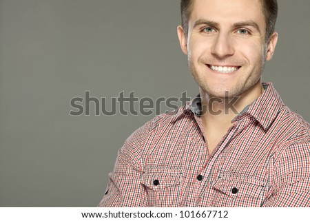 Closeup of smiling man, over gray background