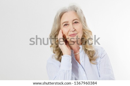 Closeup of smiling senior woman wrinkle face and gray hair. Old mature lady touching her wrinkled skin isolated on white background. Copy space