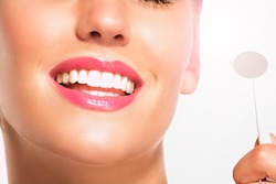 Closeup of smiling woman with perfect white teeth on white