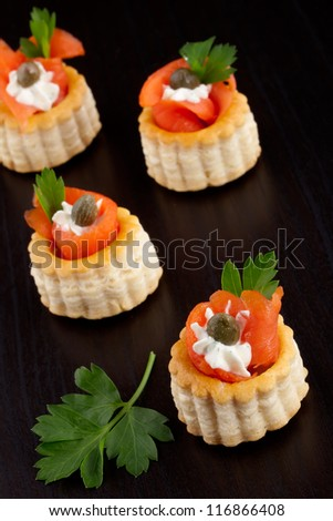 Closeup of smoked salmon canape with capers and parsley over black background.