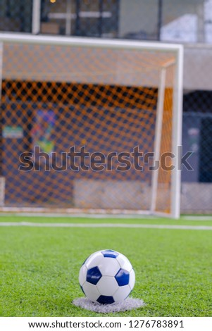 Closeup of  Soccer ball on the point of  penalty with goal background at indoor stadium football club,Selective focus. #1276783891