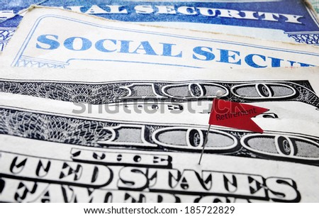 Closeup of Social Security cards and money with Retirement flag