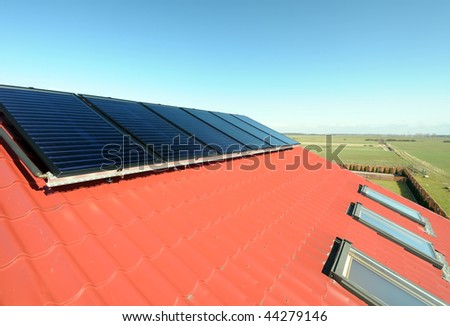 Closeup of solar panels on red roof with small windows. Blue sky and green field in background.