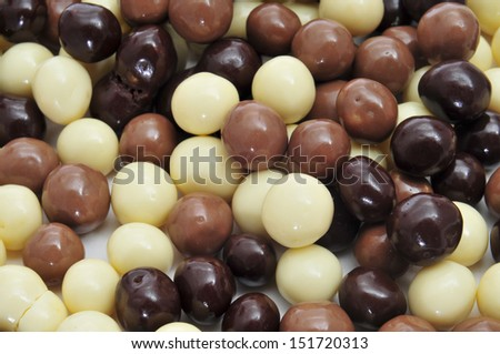 closeup of some different ball-shaped chocolates made with black chocolate, white chocolate and milk chocolate