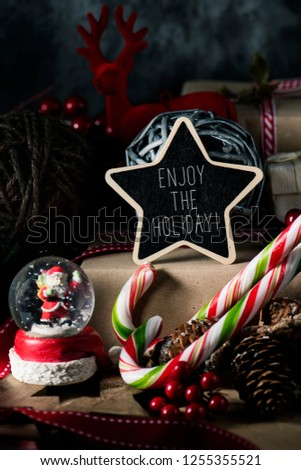 closeup of some gifts, some candy canes and some different cozy christmas ornaments, and a black star-shaped signboard with the text enjoy the holiday written in it