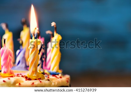 closeup of some unlit candles and just one lit candle after blowing out the cake