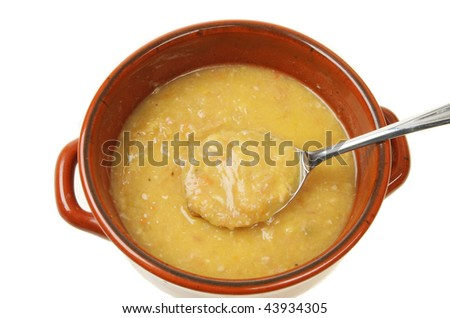 Closeup of soup with a spoon in an earthenware bowl - stock photo