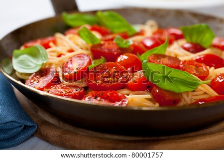 Closeup of spaghetti with cherry tomatoes and basil on a rustic pan