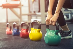 Closeup of sport young woman workout with kettlebell in gym. Healthy and strong people concept.