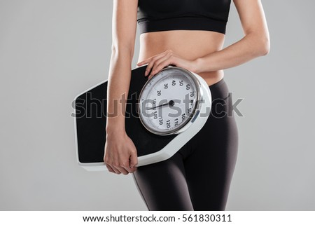 Closeup of sportswoman standing and holding weighing scale over gray background