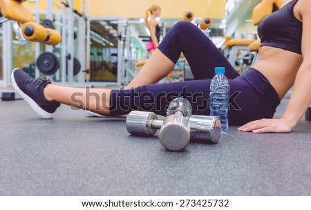 Closeup of sporty woman resting sitting on the floor of fitness center and female friend doing exercises with dumbbells in the background. Selective focus on a dumbbells.