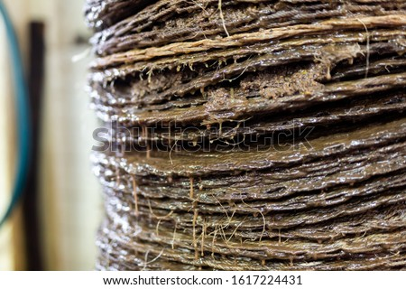 Closeup of stack of fiber mats with grinded olive paste during pressing of olive oil on artisanal factory