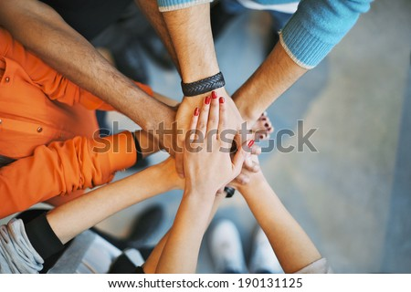 Closeup of stack of hands. Young college students putting their hands on top of each other symbolizing unity and teamwork.