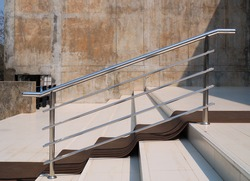 Closeup of stainless steel handrail installed on stair in front of building.