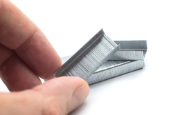 Closeup of staples pile in hand on white background