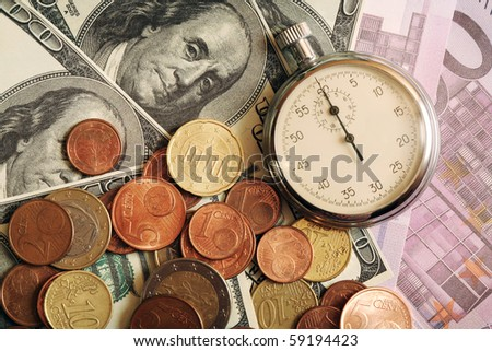 Closeup of stopwatch lying on background made from bank notes and coins