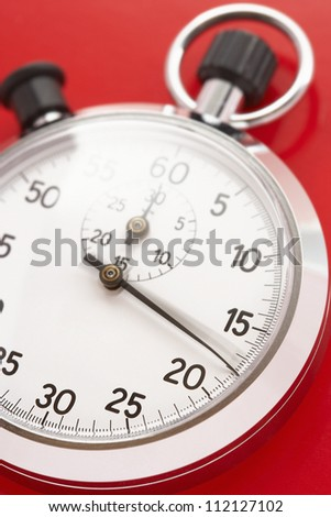 Closeup of stopwatch over red background