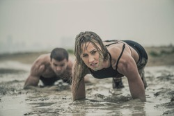 Closeup of strong athletic woman crawling in wet muddy puddle with mud on her face in an extreme competitive sport with a man close behind her