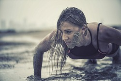 Closeup of strong athletic woman crawling in wet muddy puddle with mud on her face in an extreme competitive sport