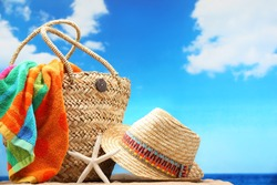 Closeup of summer beach bag and straw hat on sandy beach.