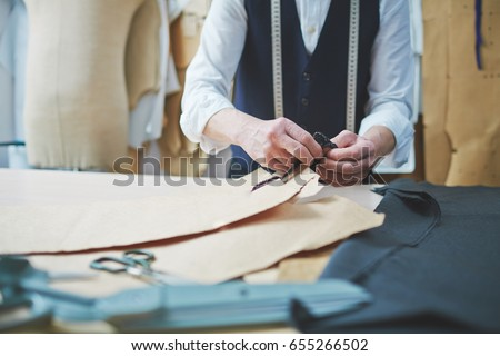 Closeup of tailors hands fitting clothing patterns while working in atelier shop