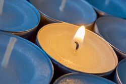 Closeup of tea lights with one being lit. A single warm orange flame between  candles in blue shadow. Christmas, mourning, condolence, memorial, funeral or cremation ceremony concept.