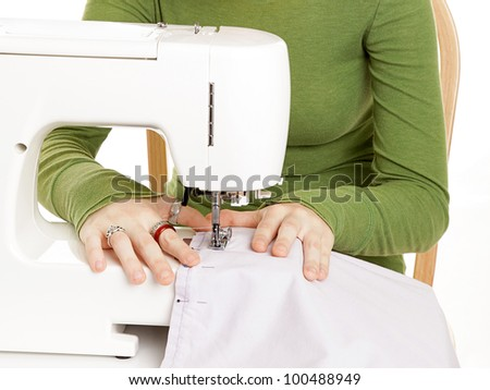 Closeup of teen girl's hands using a sewing machine.