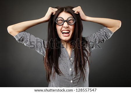 Closeup of teenage nerd shouting angry pulling her hair over gray background