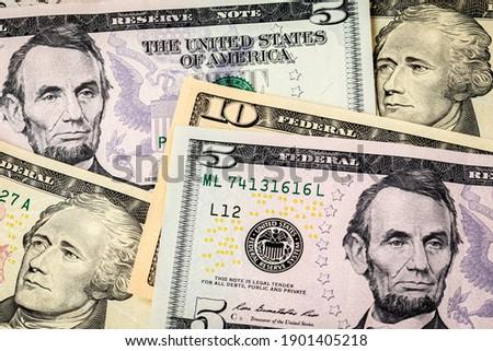 Closeup of ten and five dollar bills. Concept of 15 dollar federal minimum wage increase. Stock photo ©