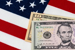 Closeup of ten and five dollar bills with American flag.  Concept of 15 dollar federal minimum wage increase