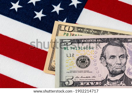 Closeup of ten and five dollar bills with American flag.  Concept of 15 dollar federal minimum wage increase Stock photo ©