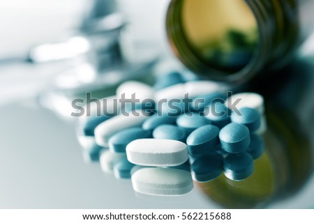 closeup of the desk of a doctors office with a bottle with pills in the foreground and a stethoscope in the background