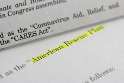 Closeup of the documents of both the Cares Act (Coronavirus Aid, Relief, and Economic Security Act) and the American Rescue Plan Act (ARPA) of 2021.