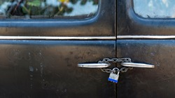 Closeup of the door of a old car, steel door locked with a padlock and a chain.