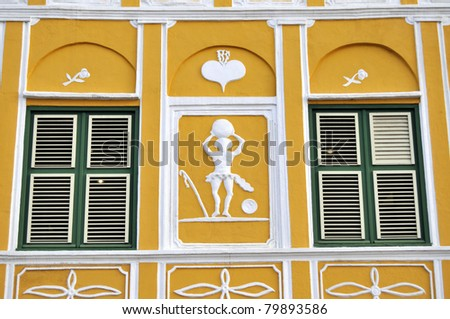 Closeup of the facade of a yellow colonial house in Willemstad, the capital of Curacao, in the Caribbean. Downtown Willemstad is a UNESCO World Heritage Site.