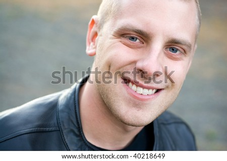 Closeup of the face of a happy young man with a big smile.