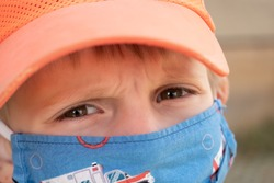 Closeup of the face of a little boy in a face mask, frowning