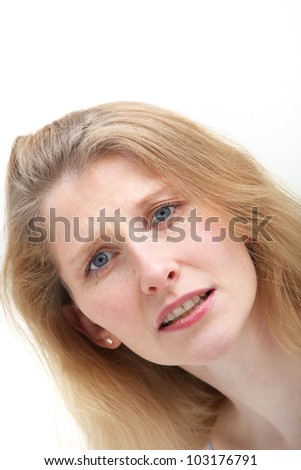 Closeup of the facial expression of a compassionate middle-aged woman with a look of caring unease peering down at the camera isolated on white