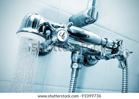 closeup of the faucets of a shower with a shower hand
