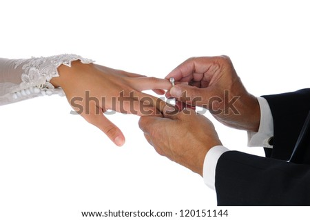 Closeup of the groom placing a wedding ring on the brides hand. Horizontal format over a white background.