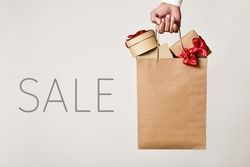 closeup of the hand of a young caucasian man holding a paper shopping bag full of gifts and the word sale