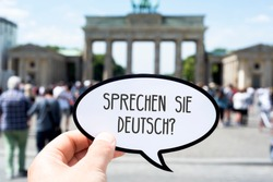 closeup of the hand of a young caucasian man showing a speech bubble with the question sprechen sie deutsch, do you speak german written in german, in front of the Brandenburg Gate in Berlin, Germany