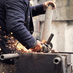 Closeup of the hands of a man processing an iron workpiece on the street with an angle grinder.