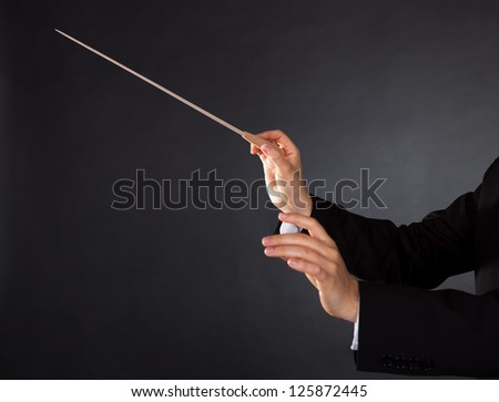 Closeup of the hands of a music conductor with a baton against a dark studio background with copyspace