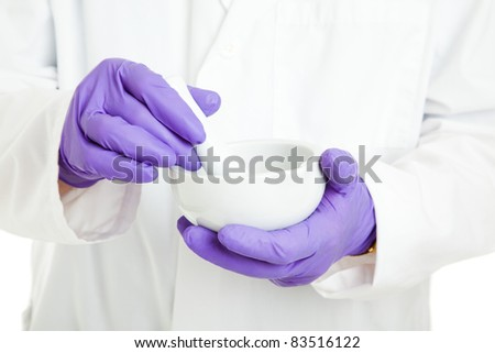 Closeup of the hands of a pharmacist or scientist, holding a mortar and pestle, and wearing rubber gloves.