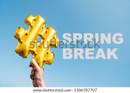 closeup of the hands of a young caucasian man holding a balloon in the shape of a hash symbol, and the text spring break, against the blue sky