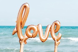 closeup of the hands of a young caucasian man on the beach holding a balloon in the shape of the word love against the sky, with the sea in the background